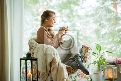Fototapeta Young woman sitting home in a chair by the window with cup of hot coffee wearing knitted warm sweater. Cozy room decorated with lanterns and candles. Scenic view of pine trees in snow in window