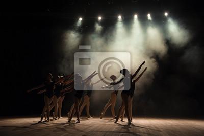 Fototapeta Zajęcia baletowe na scenie teatru ze światłem i dymem. Dzieci angażują się w klasyczne ćwiczenia na scenie.