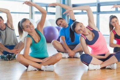 Fototapeta Zajęcia fitness i instruktor siedzi i rozciągając ręce
