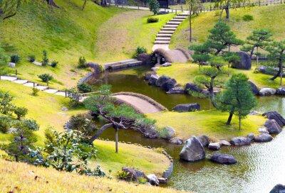 Fototapeta Zaprojektowany pagórkowate ogród skalny z małymi mostkami nad strumieniem uzwojenia, pod górę kroków, sosny