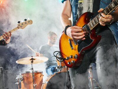 Fototapeta Zespół rockowy wykonuje na scenie. Gitarzysta, gitara basowa i perkusja. Gitarzysta w pierwszym planie. Close-up.