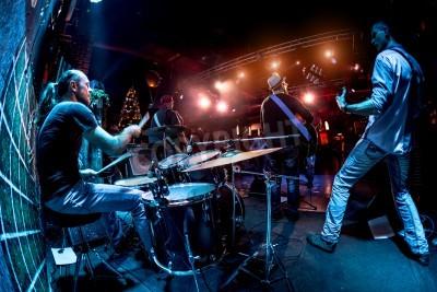 Fototapeta Zespół wykonuje na scenie, koncert muzyki rockowej. Ostrzeżenie - autentyczne strzelanie z wysokim iso w trudnych warunkach oświetleniowych. Trochę ziarna i niewyraźne efekty ruchu.