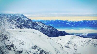 Fototapeta Zimą krajobraz z wysokich ośnieżonych gór