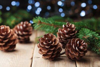 Zima wciąż życie z sosnowymi rożkami i jedlinowym drzewem na rocznika drewnianym stole. Karta z pozdrowieniami świątecznymi.