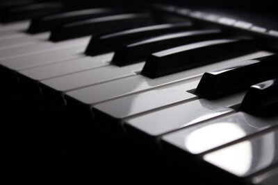 a closeup view of an electric piano midi keyboard under the bright light on black background, sol-fa concept