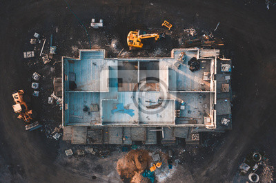 Naklejka Aerial birds eye image of the frame of a house being built on a construction site at sunset - Wooden floor and walls are visible