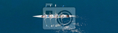 Naklejka Aerial drone top panoramic view of sport canoe rowing synchronous athletes competing in tropical exotic lake