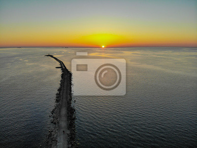 Aerial drone view of a long breakwater and sunset