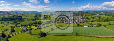 Naklejka Aerial panoramic view of typical british farmers fields and some sheep, captured with the town of Usk in  the background in South Wales, UK