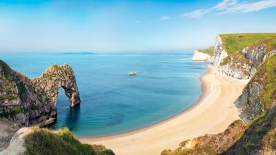 Naklejka Aerial view of Durdle Door natural formation at UNESCO heritage Jurassic Coast. The Isle of Portland can be seen on the horizon. Copy space in blue sky.