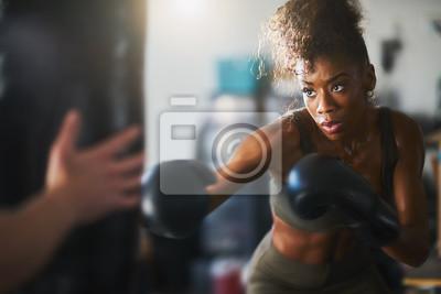 Naklejka African American kobieta uderzające worek treningowy w domowej siłowni