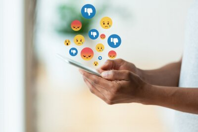 Naklejka African american person holding a tactile mobile smartphone sending text messages emoji emoticon - Black people