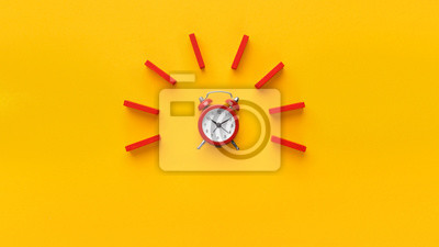 Naklejka Alarm clock with red dominoes on yellow background