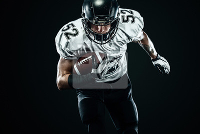 Naklejka American football sportsman player in helmet isolated run in action on black background. Sport and motivation wallpaper.