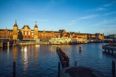 Naklejka Amsterdam, Holandia - 15 stycznia 2016: Znane budynki Amsterdam centrum miasta zbliżeniu na słońcu ustawić czas. Widok ogólny krajobrazu. Amsterdam - Holandia.