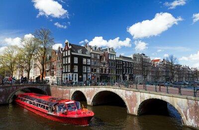 Naklejka Amsterdam kanał skrzyżowanie z czerwonej łodzi wycieczkowych w lecie z błękitne niebo