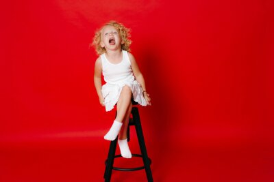 Naklejka Amuzing funny little blonde girl in white dress sitting on chair isolated on red
