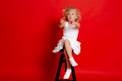 Naklejka Amuzing funny little blonde girl in white dress sitting on chair wants something isolated on red