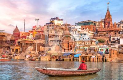 Naklejka Ancient Varanasi city architecture at sunset with view of sadhu baba enjoying a boat ride on river Ganges.