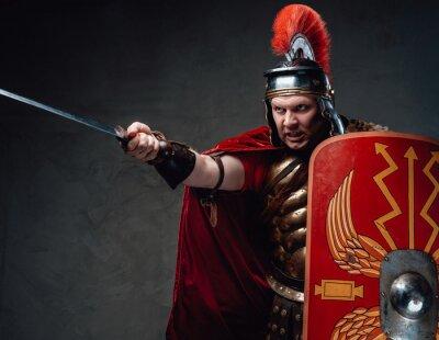 Naklejka Angry roman soldier points sword against dark background