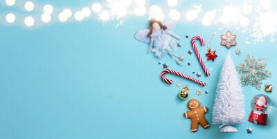 Art Christmas Holiday Background with Christmas Tree decoration on light blue background;  greeting banner flat lay backdrop picture