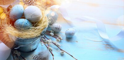 Art Happy Easter card background;  Easter eggs and spring flower branch on light blue table background