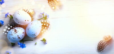 Art spring flowers and Easter eggs and bird feather on sunny wooden background; Holiday Easter banner or greeting card background