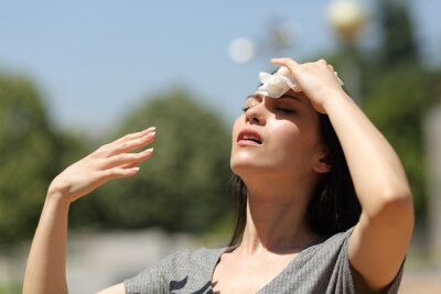 Naklejka Asian woman drying sweat in a warm summer day