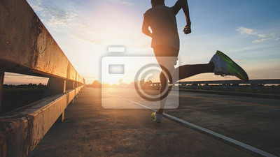 Naklejka Athlete runner feet running on road, Jogging at outdoors. Man running for exercise.Sports and healthy lifestyle concept.