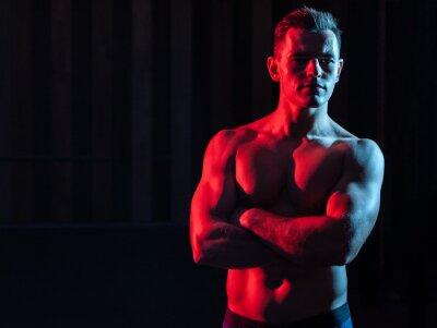 Naklejka Athletic handsome man athlete with naked torso in red blue gradient neon light on black background