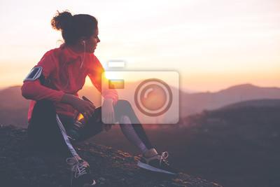 Naklejka Athletic kobieta odpoczynku po ciężkim treningu w górach o zachodzie słońca. Sport mocno ubrania.