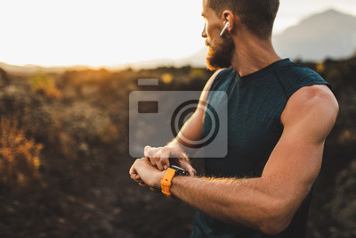 Naklejka Athletic runner start training on fitness tracker or smart watch and looking forward on horizon. Trail running and active lifestyle concept.
