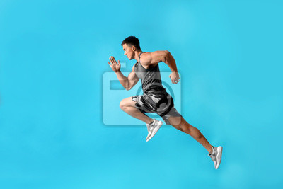 Naklejka Athletic young man running on light blue background, side view