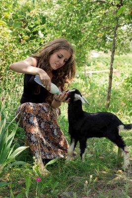 Atrakcyjna młoda kobieta jest karmienie dziecka kozę z mlekiem z butelki. orientacji pionowej.