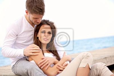 Atrakcyjna para siedzi razem na molo