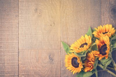 Naklejka Autumn background with sunflowers on wooden table. View from above. Retro filter effect