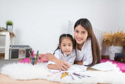 Azja dzieci szczęśliwa kochająca rodzina. całkiem młoda matka czyta książkę swoim córkom