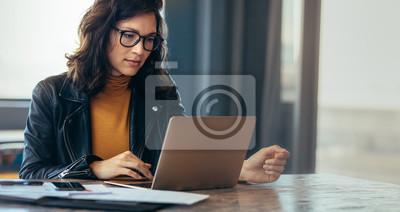 Naklejka Azjatyckiej kobiety pracujący laptop przy biurem