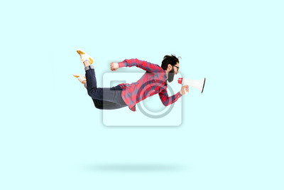 Naklejka Bearded hipster man in glasses, jumping and shouting in megaphone, photo over blue background