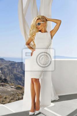 Beautiful blond woman in a wedding dress in Santorini in Greece