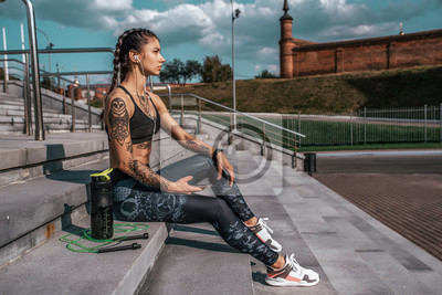 Naklejka Beautiful girl athlete in tattoos, summer city, resting after fitness workout. Sportswear leggings top. Shaker with water protein skipping rope smartphone headphones. Free space. Listening music.