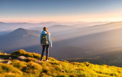 Naklejka Beautiful mountains in fog and standing young woman with backpack on the peak at sunset in summer. Landscape with sporty girl, green grass, forest, hills , blue sky with sunbeams. Travel and tourism