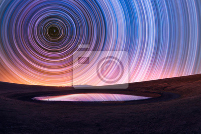 Naklejka Beautiful night landscape, old volcano, crater lake. The colorful star trails on the sky. Night timelapse photography.