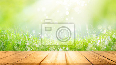 Naklejka Beautiful spring natural  background with green fresh juicy young grass and empty wooden table in nature morning outdoor.  Beauty bokeh and sunlight.