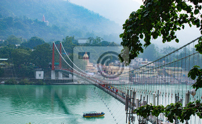 Naklejka beautiful view of Rishikesh in India 'ram jhula' and 'lakshman jhula' suspension bridge beautiful scenery with boat in the river ganges in lake in the mountains of Himalayas tourism attraction in Asia