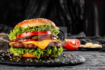Naklejka Beef burger with cheese, tomatoes, red onions, cucumber and lettuce on black slate over dark background. Unhealthy food