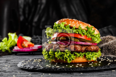 Naklejka Beef burger with tomatoes, red onions, cucumber and lettuce on black slate over dark background. Unhealthy food