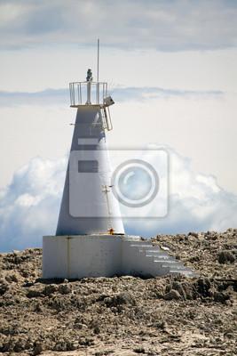 Biała latarnia morska na skale. Białe chmury w tle.