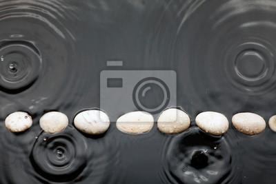 Białe kamienie w wodzie w deszczu