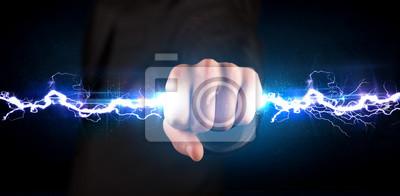 Naklejka Biznes człowiek trzyma śrubę światła na energię elektryczną w dłoniach